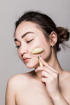 Beleza rosa pedra jade rosto rolo para massagem facial terapia isolada na parede cinza. retrato de mulher asiática.