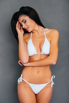 Beleza sensual. mulher jovem e atraente em biquíni branco tocando seu cabelo e mantendo os olhos fechados em pé contra um fundo cinza