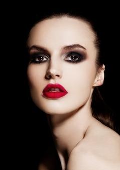 Beleza smokey olhos lábios vermelhos maquiagem modelo em fundo preto