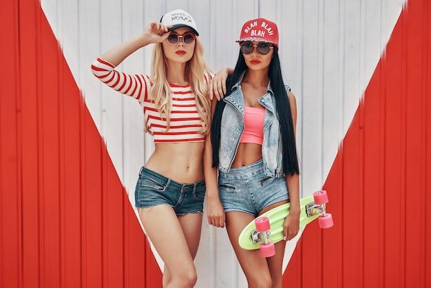 Belezas elegantes. duas belas moças de boné e óculos escuros segurando um skate e olhando para a câmera em pé contra um fundo colorido