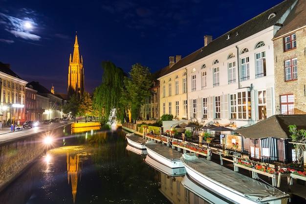 Bélgica, bruges, antiga cidade europeia, paisagem urbana à noite com vista sobre a igreja e o rio. turismo e viagens, famoso marco da europa, lugares populares, flandres ocidental, benelux