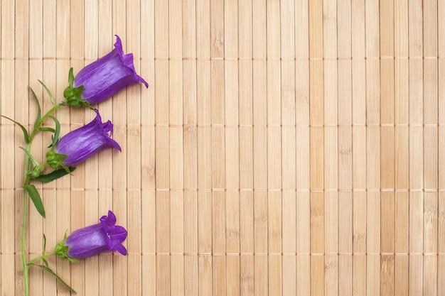 Bellflower de cor ultramarine em fundo de guardanapo de bambu bege