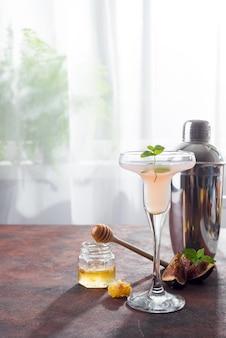 Bellini coquetel com pêssego e figos, mel na luz de fundo sobre windows, copie o espaço