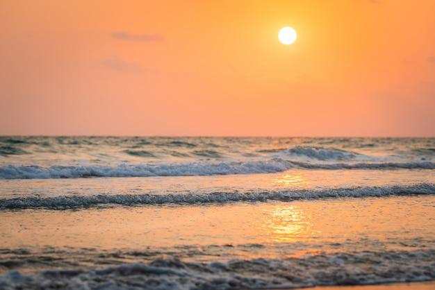 Belo amanhecer com pôr do sol e bela praia, onda suave e clara sobre a praia arenosa