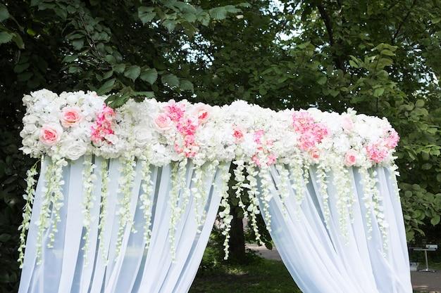 Belo arco branco com enfeites de flores para a cerimônia de casamento com cadeiras para convidados no fundo verde com árvores