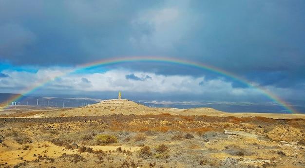 Belo arco-íris em local árido, com moinhos de vento e montanhas ao fundo.