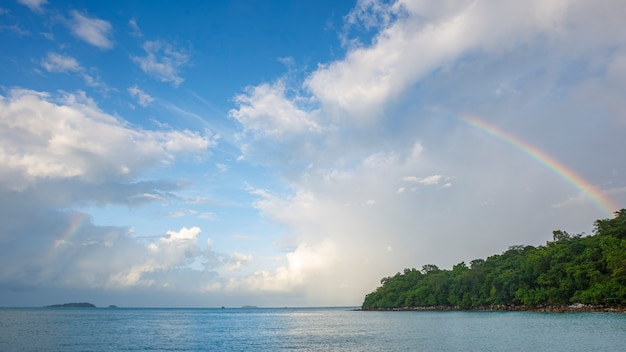 Belo arco-íris no céu na praia tropical após a chuva
