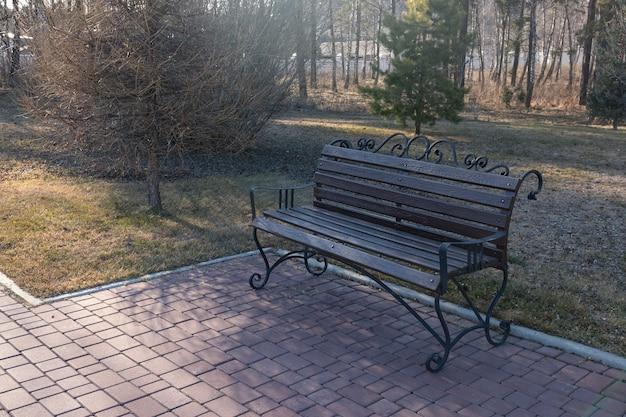 Belo banco de madeira com elementos de ferro forjado no parque. melhoria do paisagismo