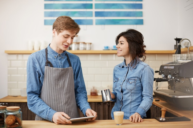 Belo barista feminino fazendo café raf sorrindo alegremente, olhando feliz.
