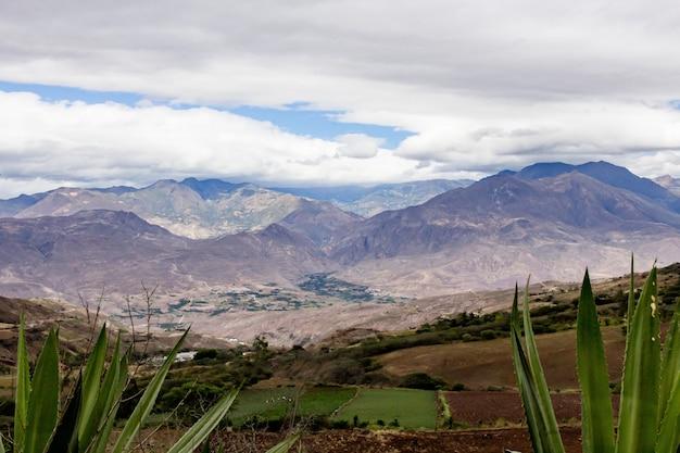 Belo campo com incríveis montanhas rochosas e colinas e céu nublado incrível
