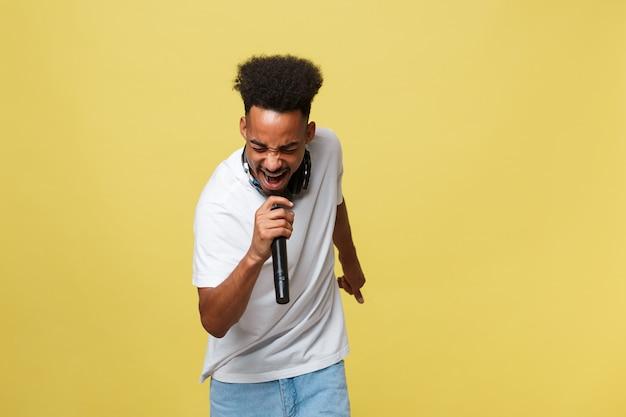 Belo cantor masculino americano africano realizando com microfone.