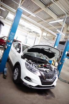 Belo carro moderno com capô aberto em um posto de gasolina em processo de reparo