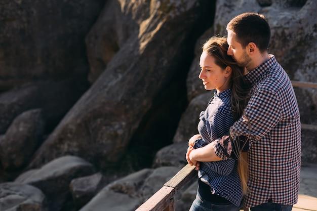 Belo casal abraçando e desfrutando de um dia ventoso de outono em rochas