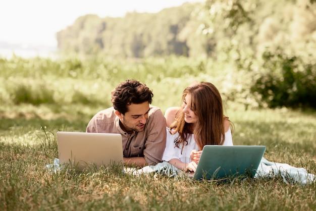 Belo casal adolescente homem e mulheres trabalhando usam laptop para trabalhar no parque ao ar livre férias