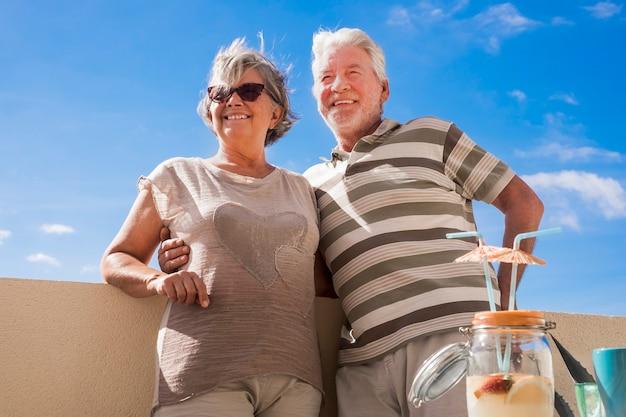 Belo casal adulto maduro caucasiano sorrir e desfrutar da atividade de lazer ao ar livre, juntos, no terraço em casa. bebida de frutas de estilo de férias com guarda-chuva em cima da mesa. conceito de felicidade para reti