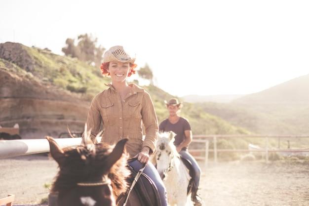 Belo casal caucasiano amigos jovens cavalgam lindos cavalos ao ar livre em uma escola. luz de fundo do sol para imagem brilhante em filtro quente. cena amigável com mulher e homem aprendem a andar juntos