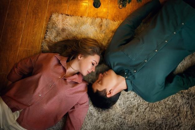 Belo casal caucasiano de meia idade encontra-se no tapete aconchegante. vista do topo. efeito de grão de filme