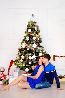 Belo casal com roupas azuis sentado no chão perto da árvore de natal verde