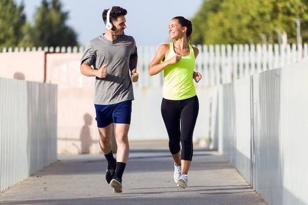 Belo casal correndo na rua.