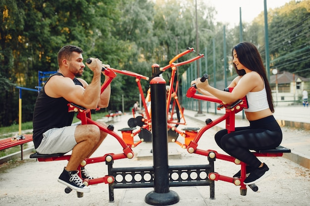 Belo casal de treinamento em um parque de verão