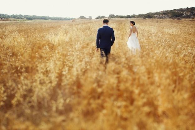 Belo casal em caminhada romântica correndo e sorrindo no campo de verão.