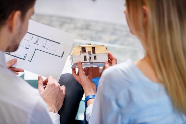 Belo casal jovem discutindo o modelo 3d e o esboço da futura casa.