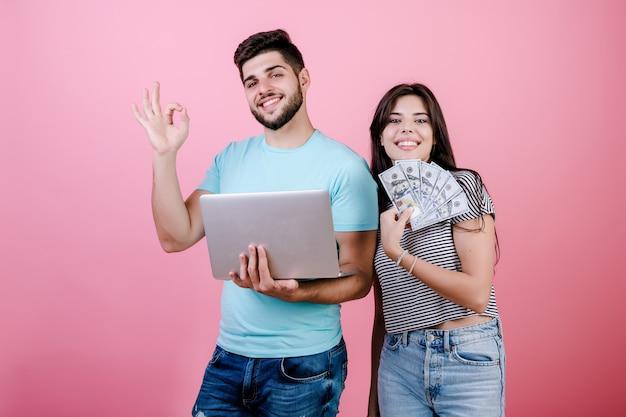 Belo casal jovem rico homem e mulher com notas de laptop e dólar