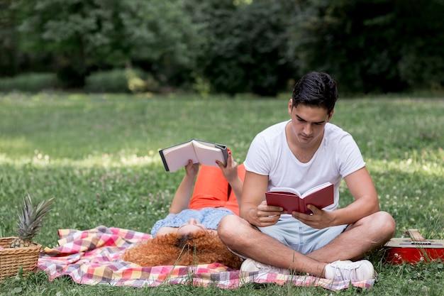 Belo casal lendo livros e piqueniques