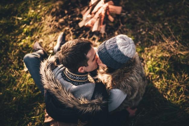 Belo casal relaxante perto da fogueira na floresta no entardecer