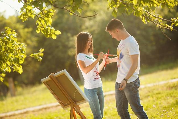 Belo casal se divertindo ao ar livre ao ar livre. desenho do homem novo e da mulher por pinturas coloridas em se t-shirt do `s com as escovas perto do cavalete na natureza.