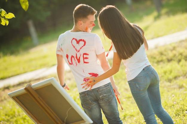 Belo casal se divertindo ao ar livre ao ar livre. jovem e desenho de mulher por tintas coloridas em camisetas um do outro com as mãos perto do cavalete na natureza.