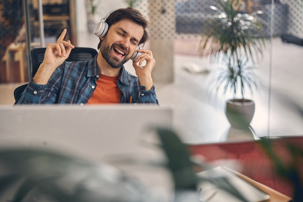 Belo cavalheiro barbudo com fones de ouvido sem fio curtindo suas músicas favoritas enquanto está sentado à mesa no escritório