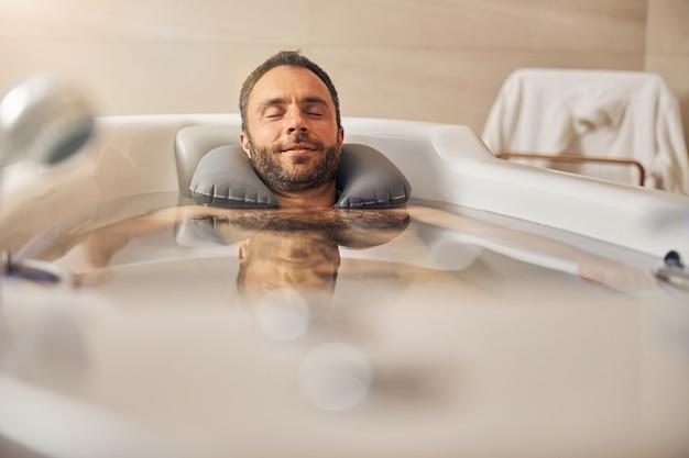 Belo cavalheiro de olhos fechados relaxando na banheira e sorrindo durante o procedimento de hidroterapia