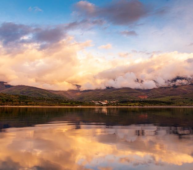 Belo cenário de formações de nuvens fofas acima das montanhas refletindo no lago