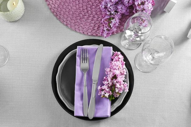 Belo cenário de mesa com talheres de prata e lilás como decoração floral
