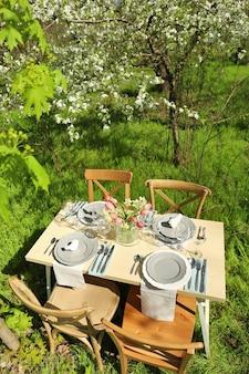 Belo cenário de mesa com vaso de flores no jardim