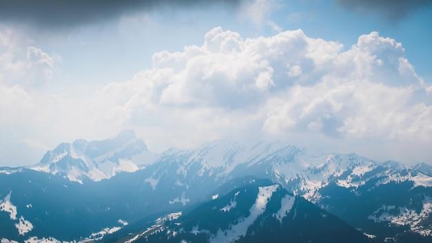 Belo cenário de nuvens brancas e fofas cobrindo altas montanhas durante o dia