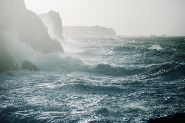 Belo cenário de ondas do mar batendo em formações rochosas
