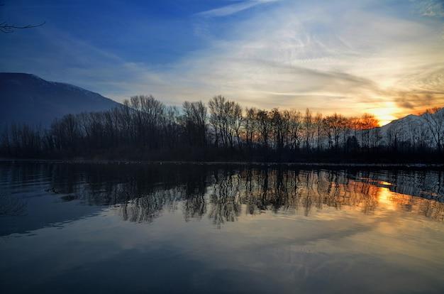 Belo cenário de pôr do sol sobre o lago com silhuetas de árvores refletidas na água