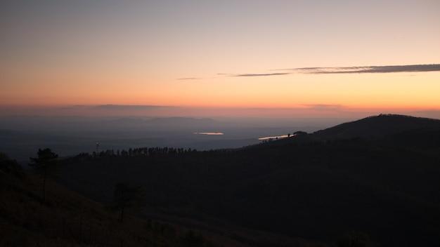 Belo cenário de uma paisagem com montanhas com um pôr do sol de tirar o fôlego ao fundo.