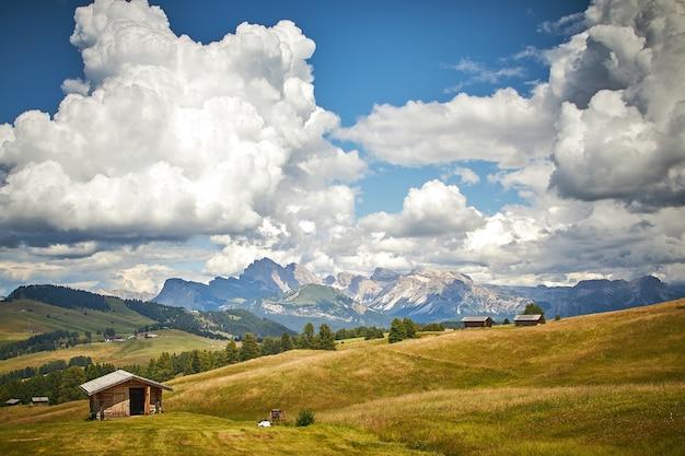 Belo cenário de uma paisagem verde com altos penhascos rochosos sob nuvens brancas na itália