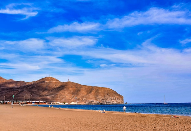 Belo cenário de uma praia com uma enorme formação rochosa nas ilhas canárias, espanha