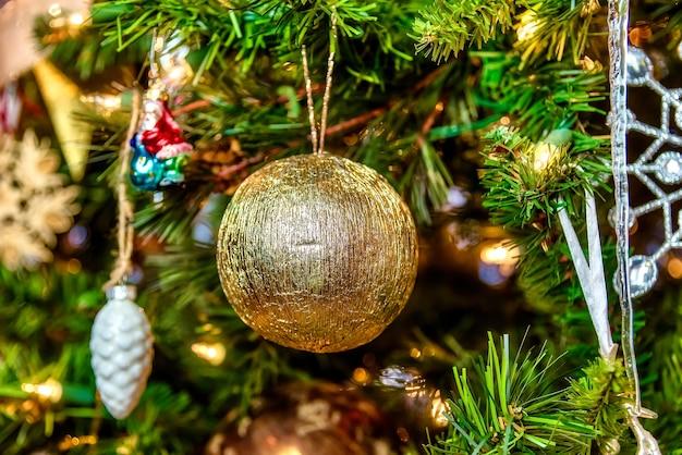 Belo close de uma bola dourada e outras decorações em uma árvore de natal com luzes