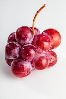 Belo close-up de cacho de uvas vermelhas (tintas) na mesa. gotas frescas, cruas e de água.