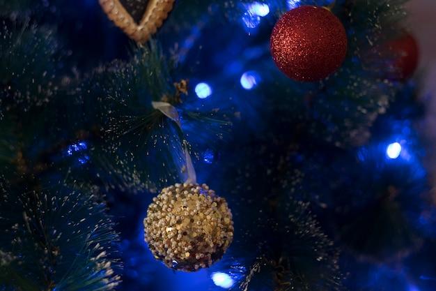Belo close-up de uma árvore de natal com ligts azuis e bolas douradas.