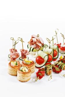 Belo conjunto de canapés para uma pessoa com legumes, queijo, frutas, bagas, salame, frutos do mar, carne e decoração