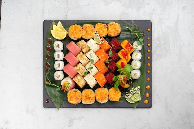 Belo conjunto grande de diferentes tipos de sushi maki em uma placa de pedra retangular preta.