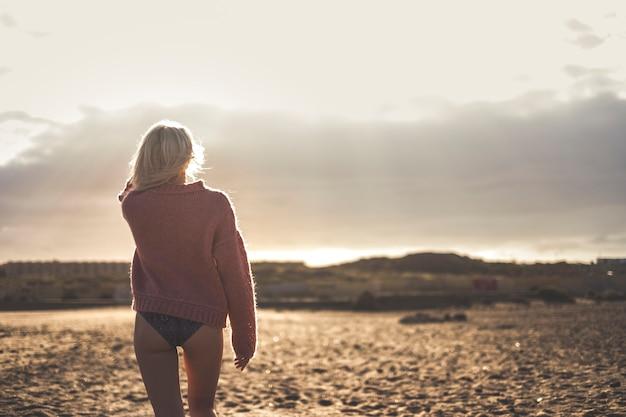 Belo corpo e modelo loira sexy indo embora e visto de trás. hora do pôr do sol e atividade de lazer ao ar livre na praia para férias e viajar sozinho conceito