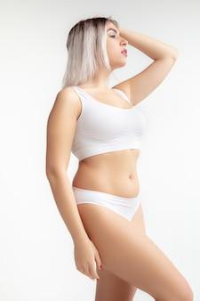 Belo corpo feminino em roupa interior isolado no branco.