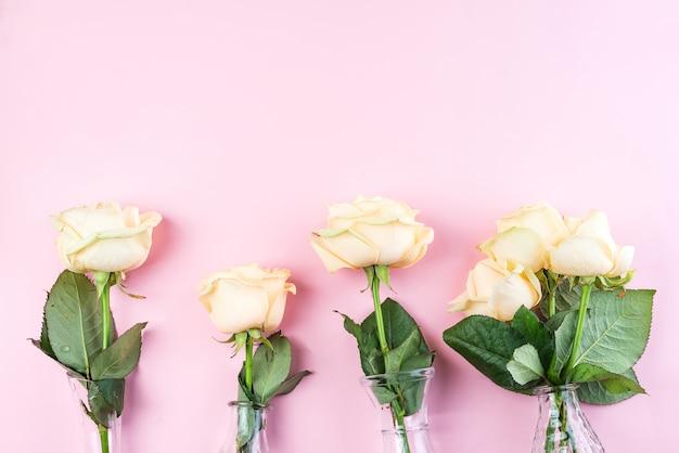 Belo corte fresco bege rosas em vaso de vidro no fundo rosa